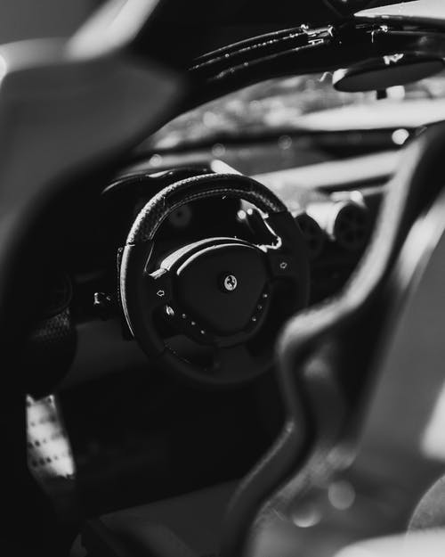 From above black and white of contemporary style automobile interior with steering wheel with buttons
