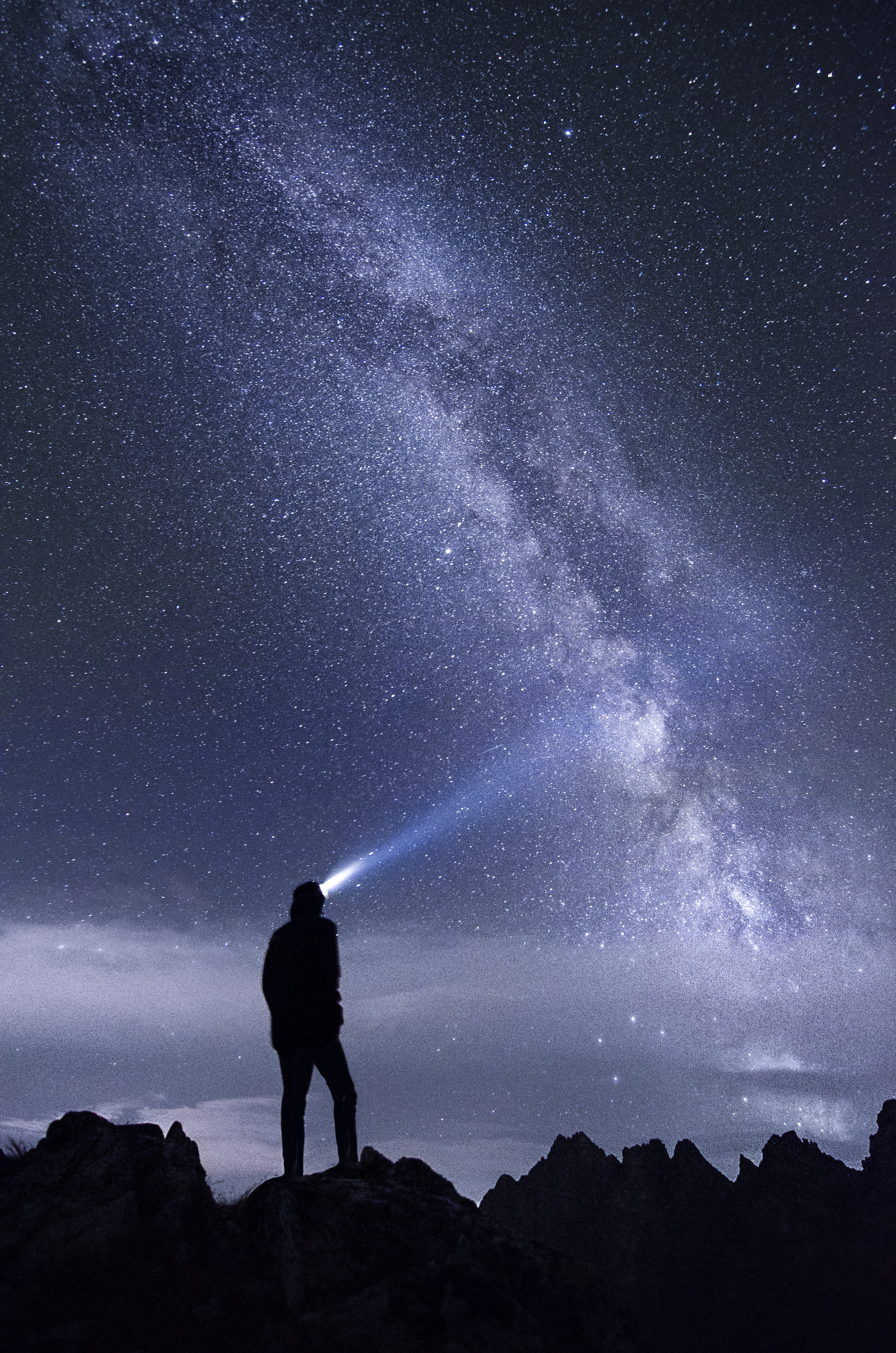 Silhouette of Man Standing on Mountain during Night