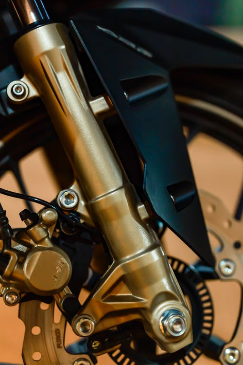 Closeup of modern motorbike wheel with brake panel and fork tube fixed with screws