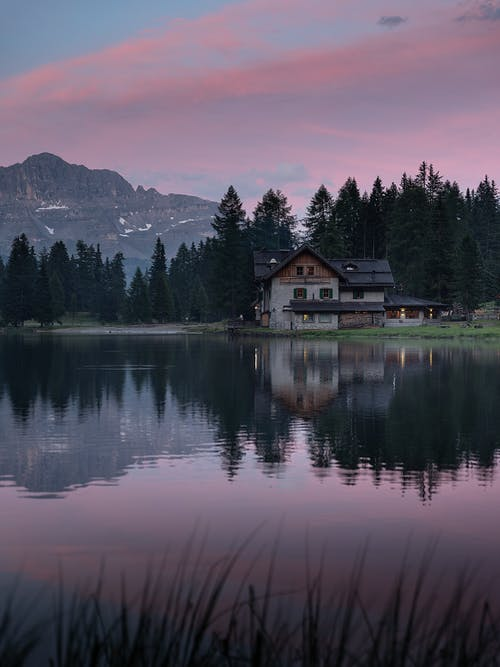 Old house reflecting in lake behind mountain at sunset