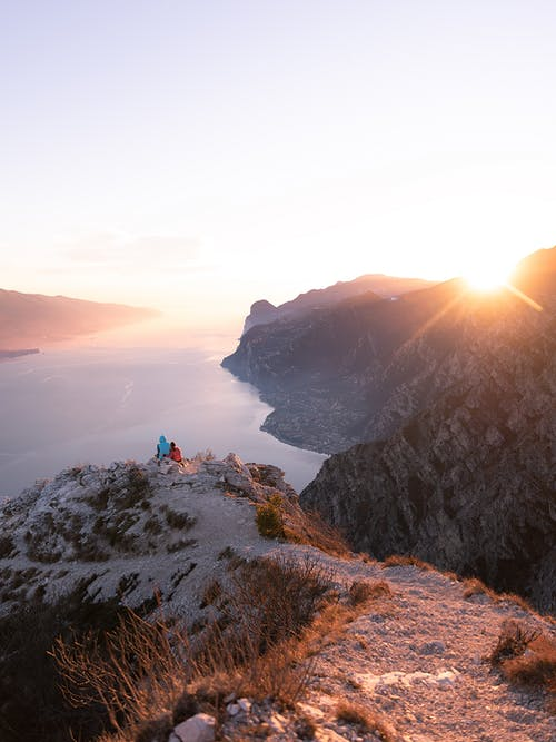 People Sitting on Cliff Edge during Sunset