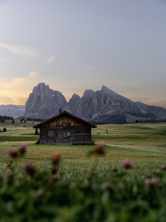 Picturesque view of aged wooden house on green lawn behind rough rocks under cloudy sky at sunset