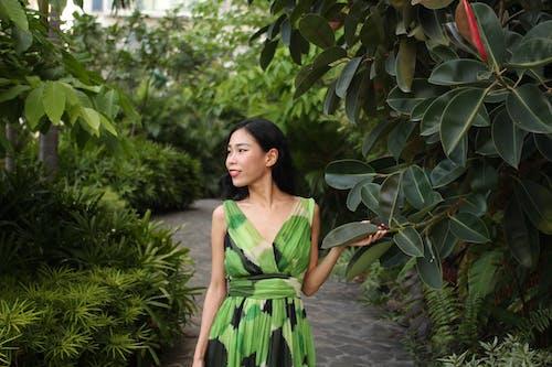 Woman in Green Sleeveless Dress Standing Near Dark Green Plants