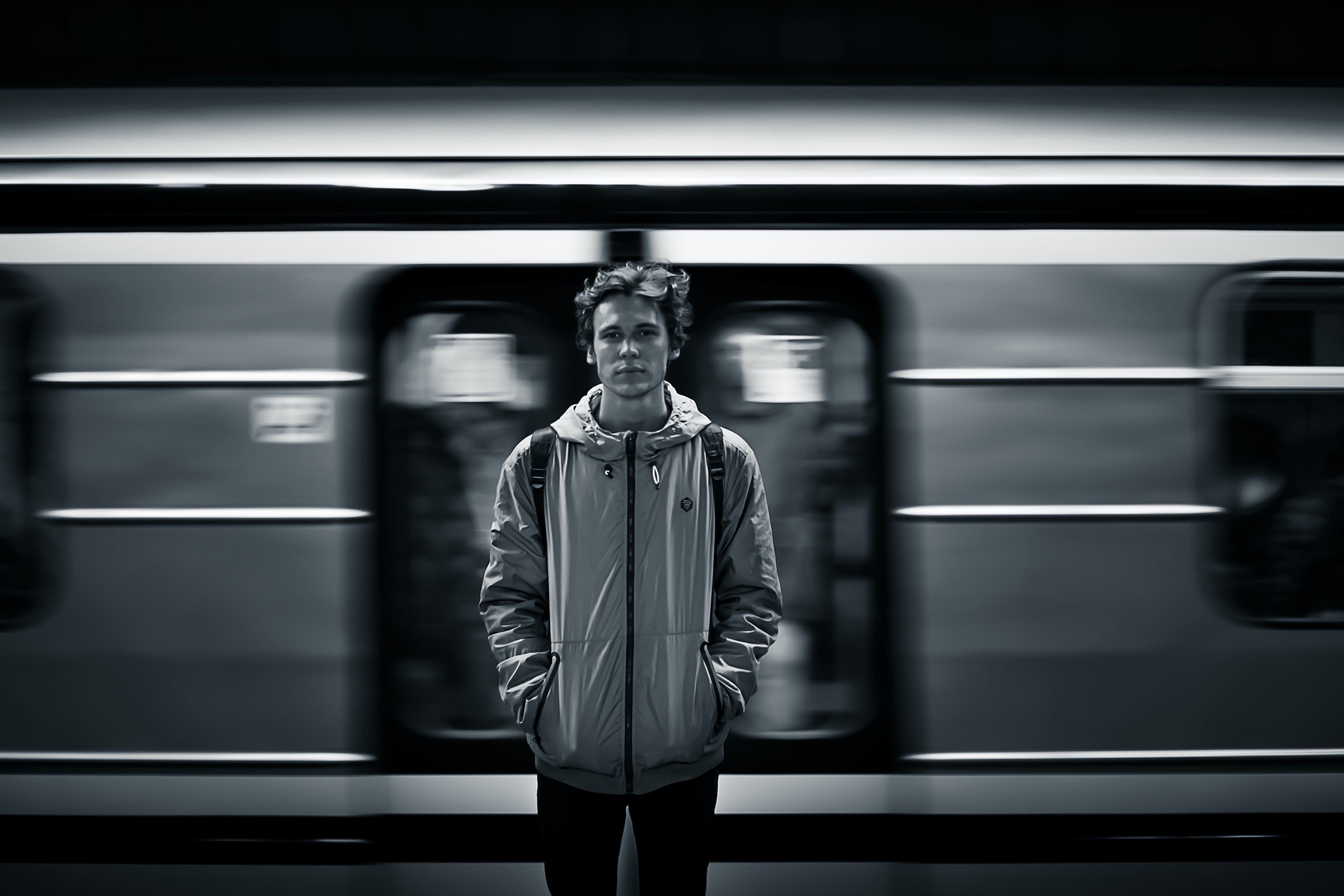 Man Wearing Windbreaker Jacket Standing on Train Station Grayscale Photography