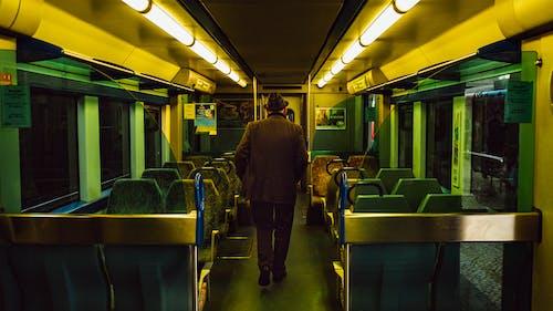 Man in Brown Coat Walking Inside the Train