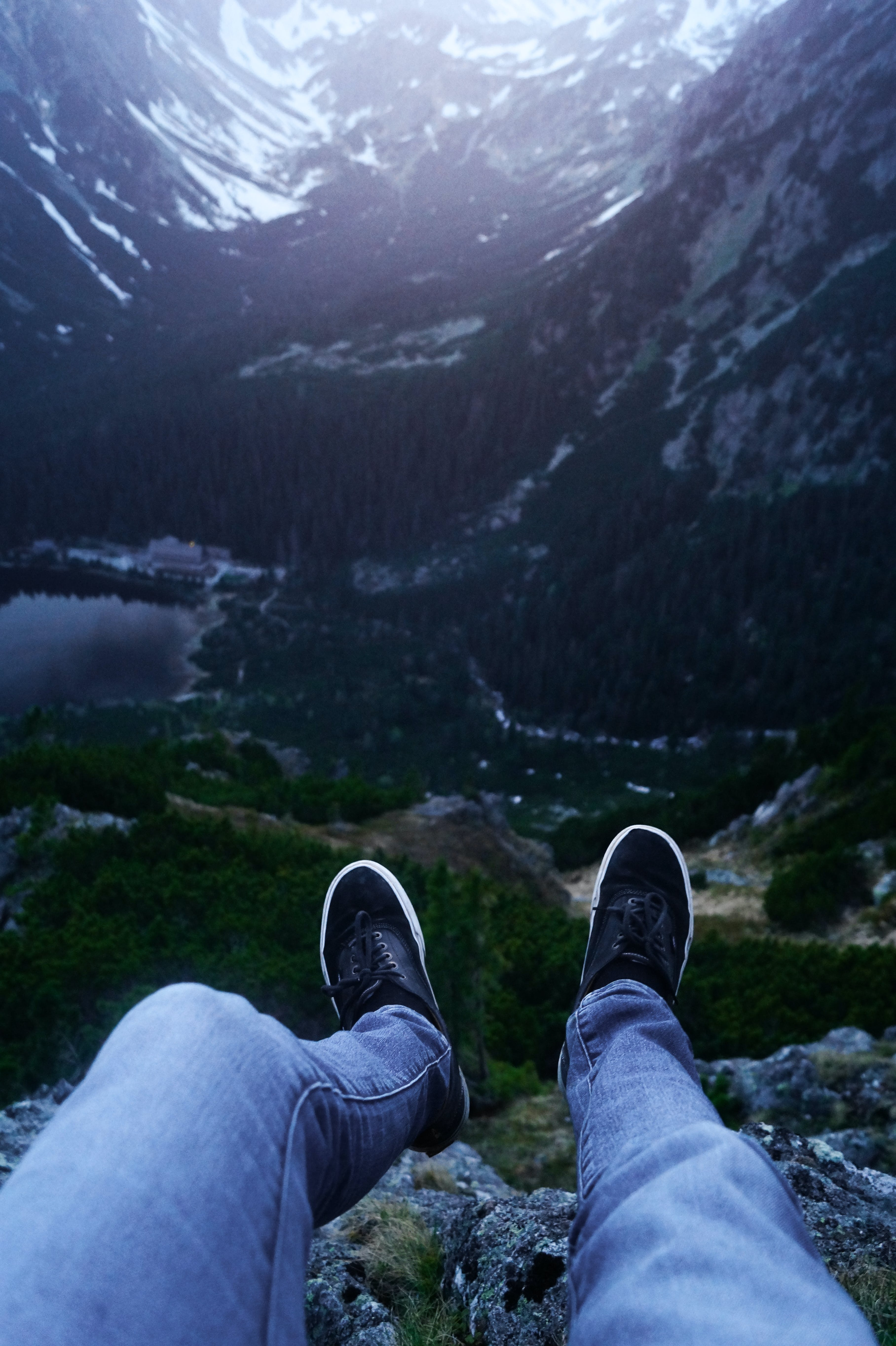 Person Wearing Denim Pants and Black Sneakers Sitting on Rock Cliff Viewing Mountains