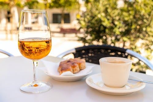 Clear Wine Glass Beside White Ceramic Plate With Food