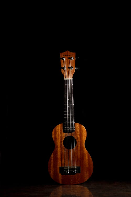 Brown Ukulele Against Black Background