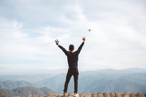 Man in Black Jacket Standing on Top of Mountain