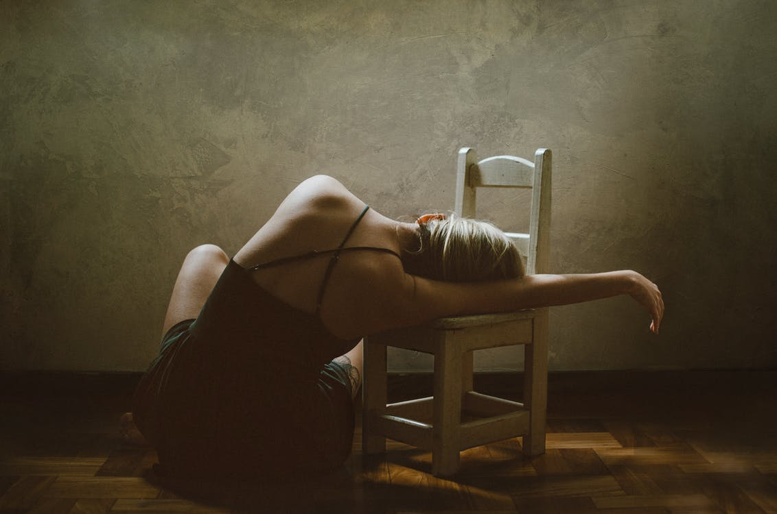Woman Sitting on Floor While Leaning on Chair