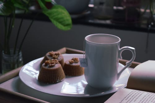 Cup of tea served with chocolate cupcakes