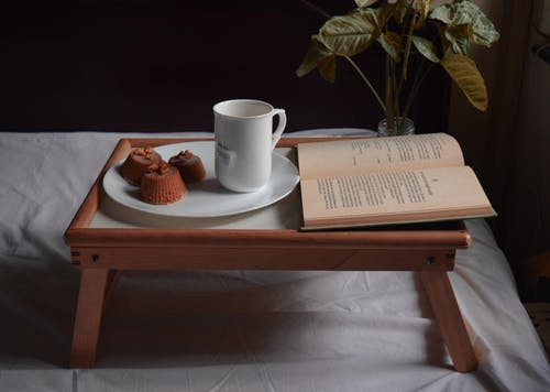 Cup of tea and dessert near book on bed tray