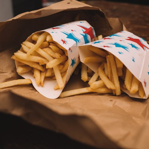 French fries in paper packages on table