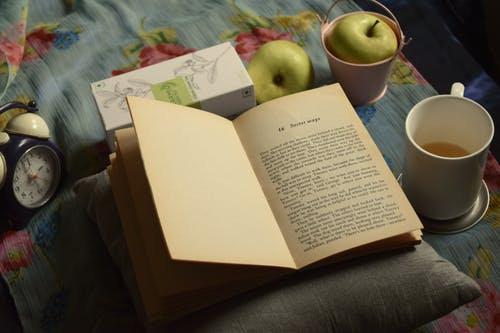 High angle composition of interesting book placed on soft pillow near cup of aromatic tea and green apples and alarm clock