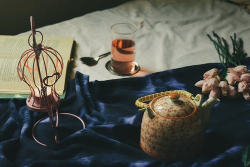Arrangement of teapot and creative hanging candleholder with burning tealight candle placed on comfy bed near opened book and glass with drink