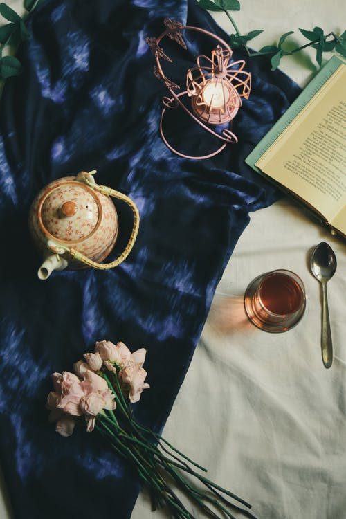 From above arrangement of ceramic teapot and glass of hot fresh tea served on blue silk cover on bed near book flowers and candleholder