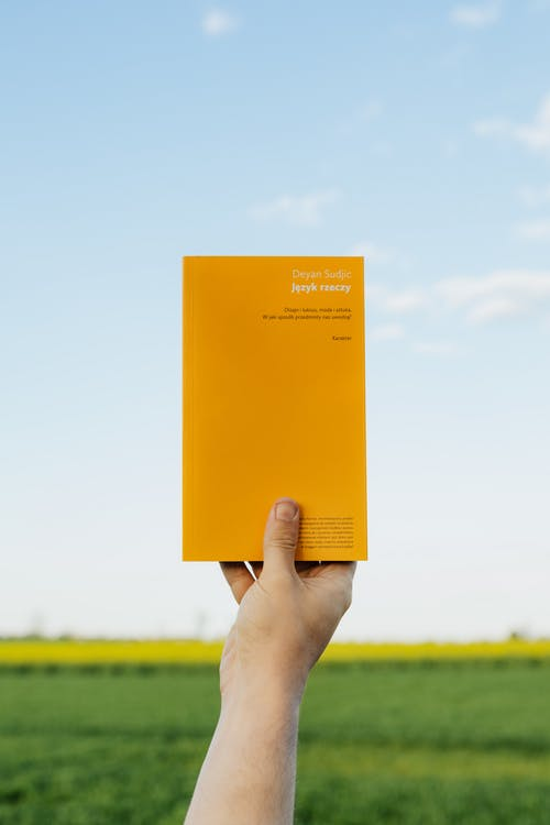 Crop person with book in summer field