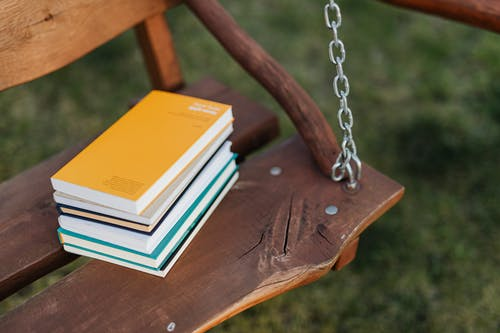 From above of pile of colorful books on wooden bench of garden swing on quiet summer evening