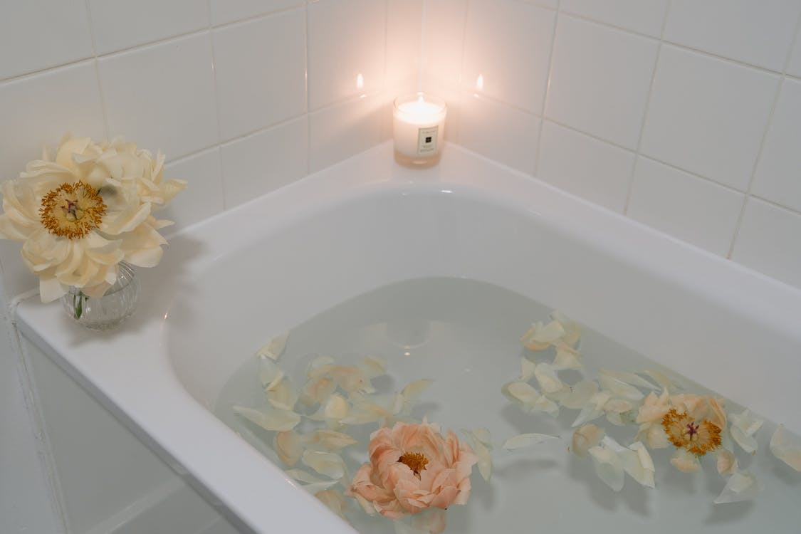 White Ceramic Bathtub With Water, candle, flowers. Perfect self-care