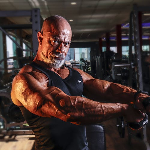 Muscular brutal male bodybuilder in sportswear performing arms exercise while working out in modern gym and looking at camera confidently