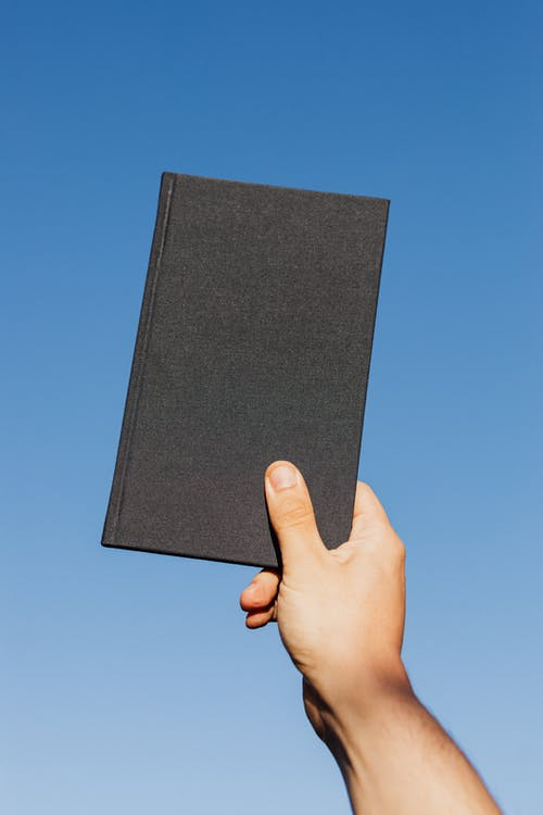 Crop unrecognizable person with closed black notebook in hand against clear blue sky