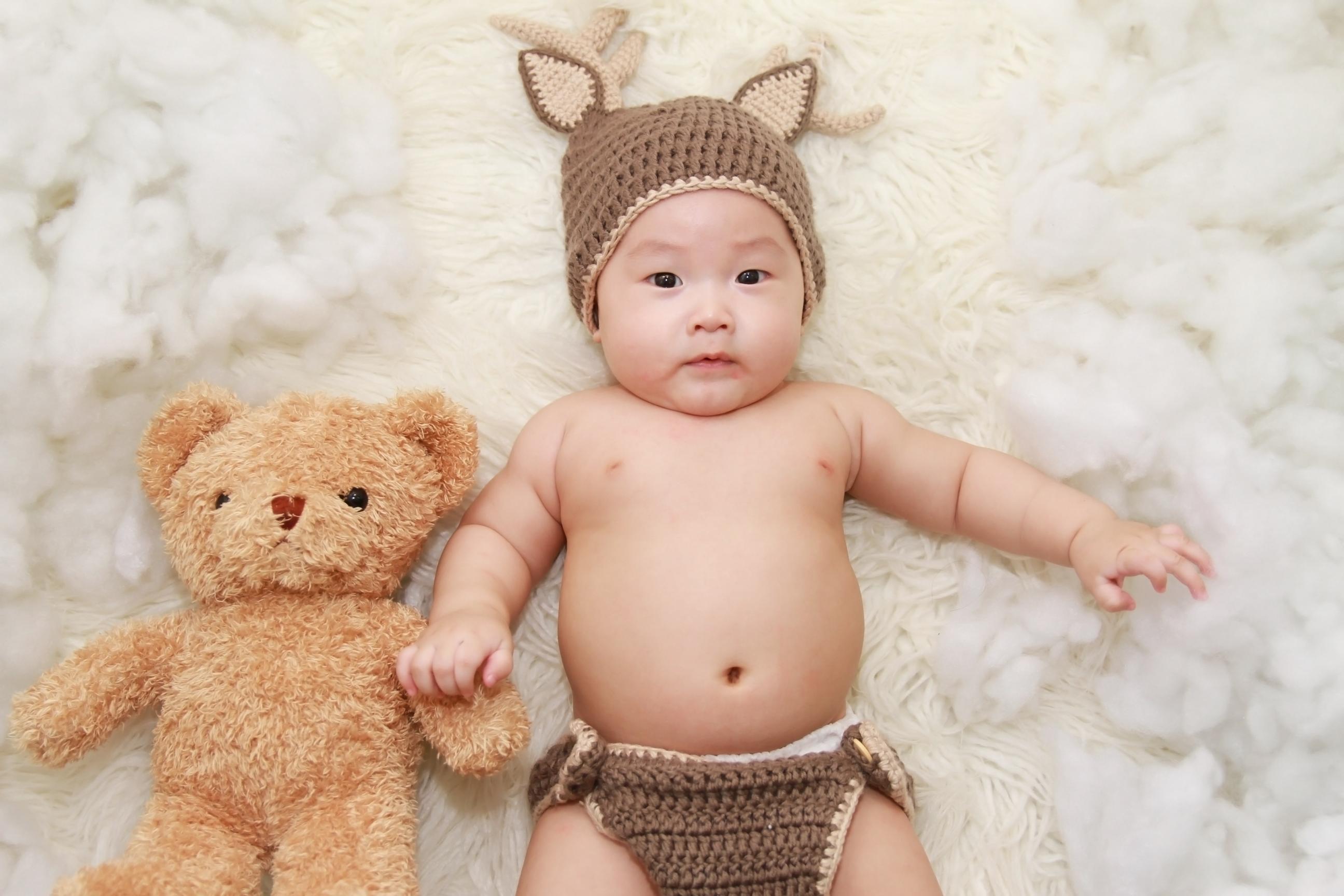 baby lying on white cushion beside brown bear plush toy