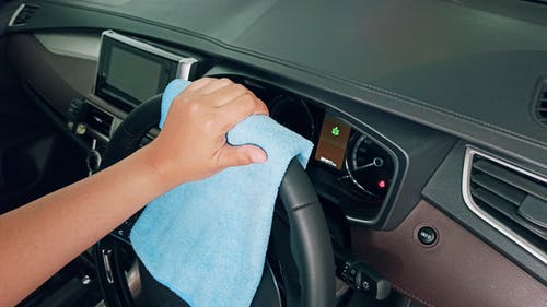 Crop person cleaning car steering wheel with fiber cloth