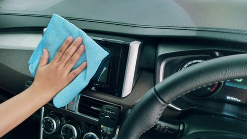 Crop person wiping modern car panel