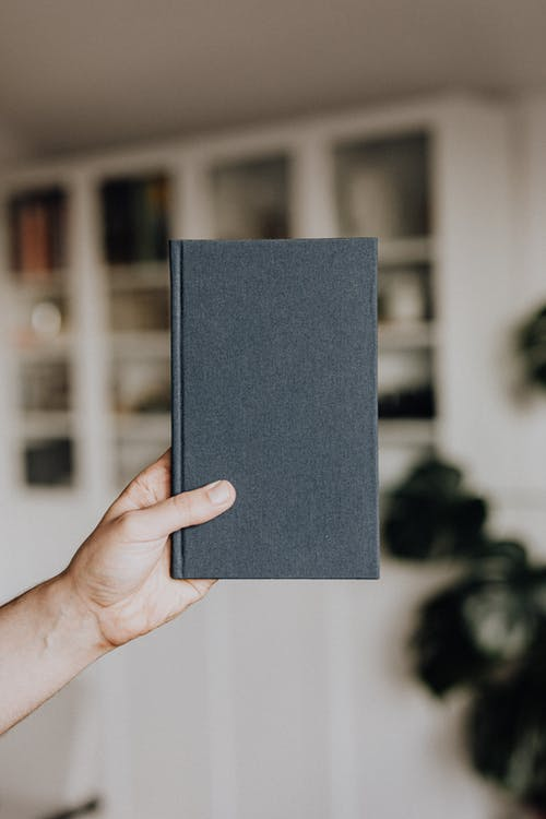 Person Holding Black Rectangular Book