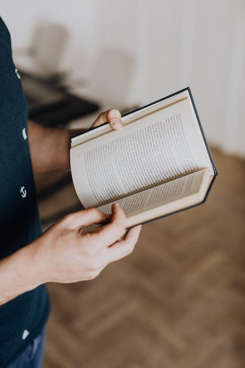 Photo of Person Holding Opened Book