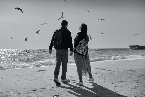Man and Woman Walking on Beach While Holding Hands