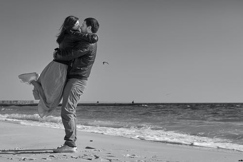 Grayscale Photo of Couple on Seashore