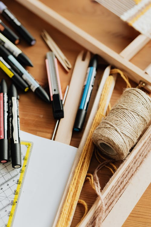 Assorted stationery scattered in wooden drawer