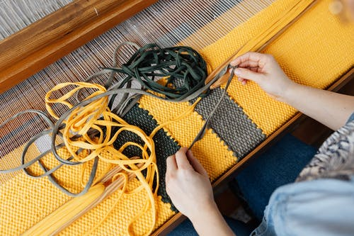 Top view of crop anonymous female employee working on wooden weaving loom machine with stretched durable colorful threads in workshop