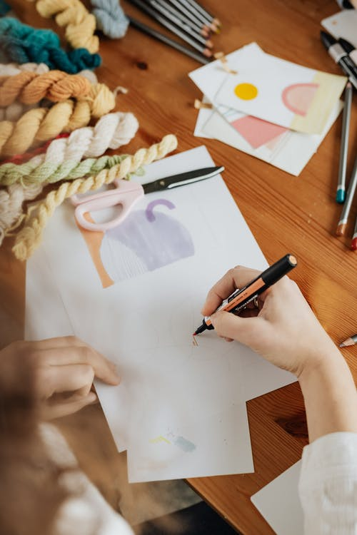 Crop unrecognizable designer using carbon paper while drawing at work