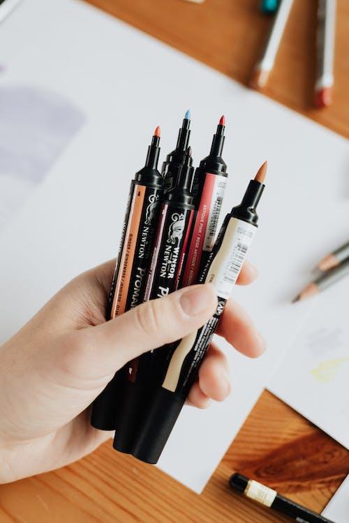Crop faceless designer demonstrating marker collection at work