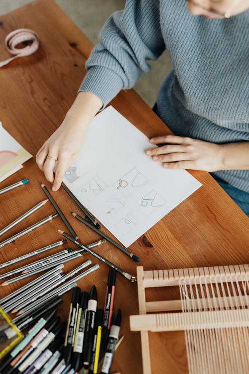 Top view of crop unrecognizable female designer in eyewear sitting at table in front of stationery and wooden weaving loom machine with sheet of paper with drafts