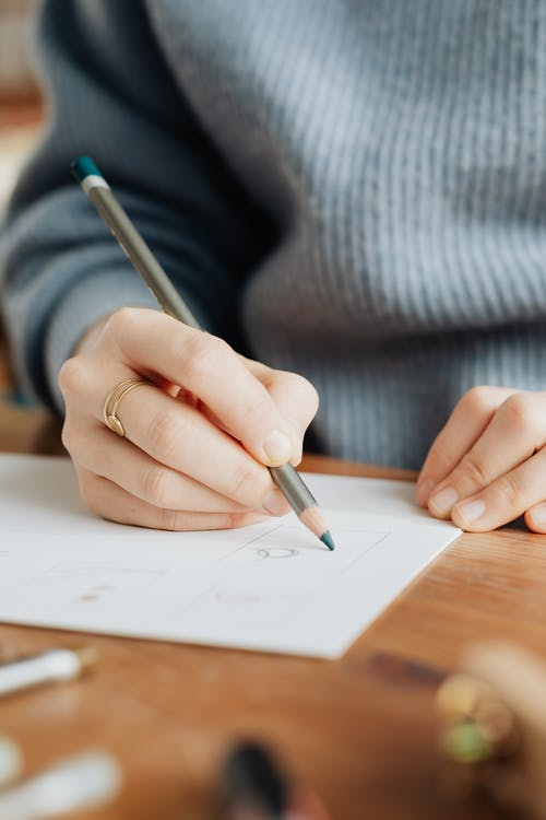 Crop unrecognizable female designer drawing on paper in office