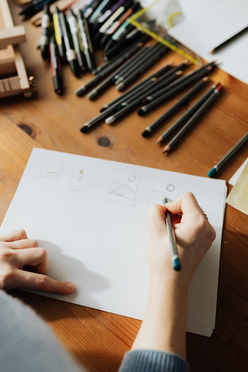Crop unrecognizable designer drawing schemes on paper using pencil