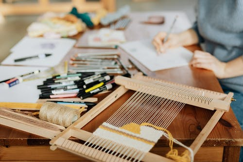Crop unrecognizable female designer making sketch on paper while sitting at desk near various markers and pencils with wooden weaving loom machine with stretched threads