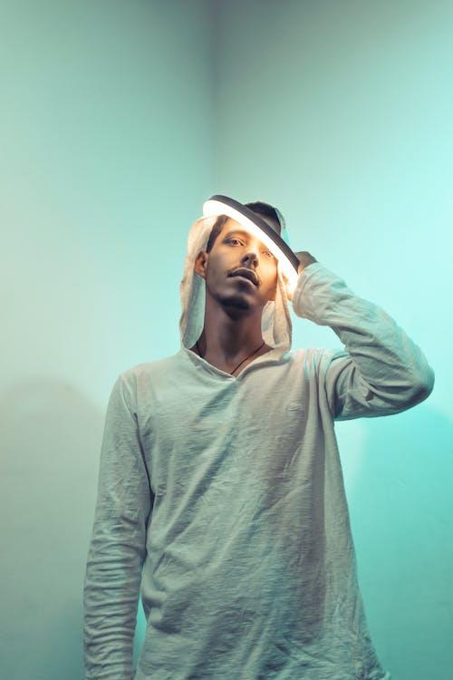 Stylish young ethnic guy with illuminated lamp on head