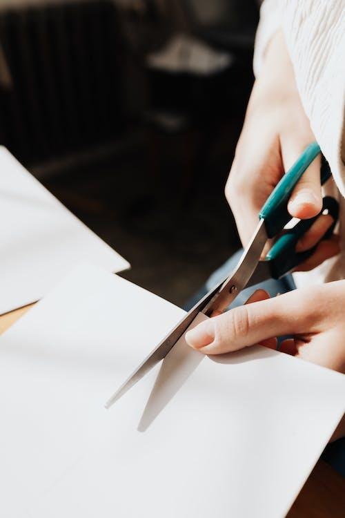 Crop young craftswoman cutting paper sheet