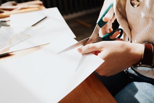 Unrecognizable young craftswoman cutting paper sheet on wooden table