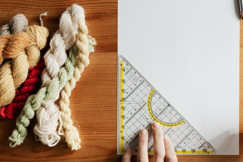 Top view of unrecognizable female weaver preparing template for future carpet on piece of paper using triangular protractor sitting at wooden table with yarn twists