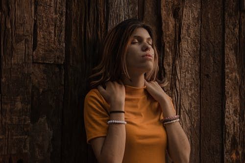 Woman in Orange Turtleneck Shirt Leaning on Brown Wooden Wall