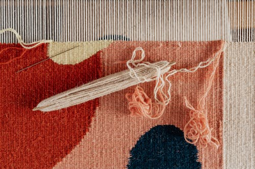 From above of shuttle and needle placed on part of handmade carpet with circle pattern on loom frame during weaving process