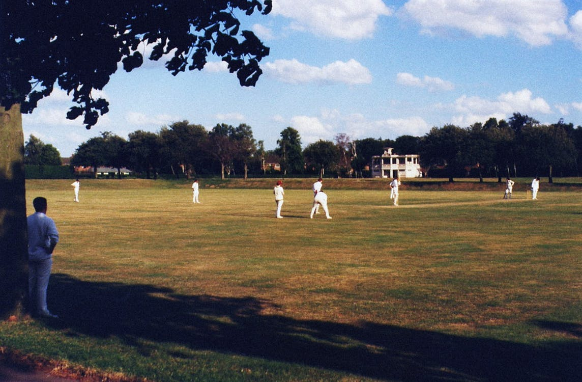 People Playing Cricket on Green Grass Field