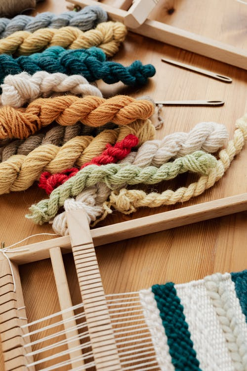 From above of unfinished tapestry on manual wooden loom placed on wooden table with assorted yarn twists and wooden needles during weaving process in workshop