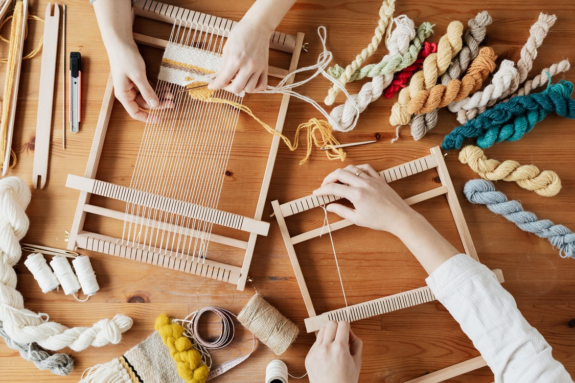 Top View Photo of Two Person's Hands Weaving