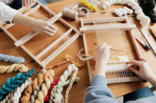 Photo of Two Person's Hands Weaving